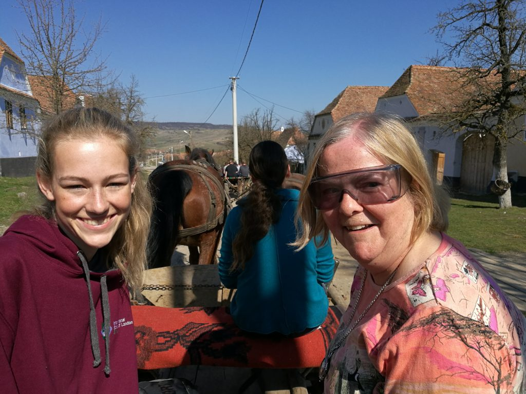 Hilary enjoying a horse drawn carriage ride with her guide, Serena, in a traditional Romanian village!
