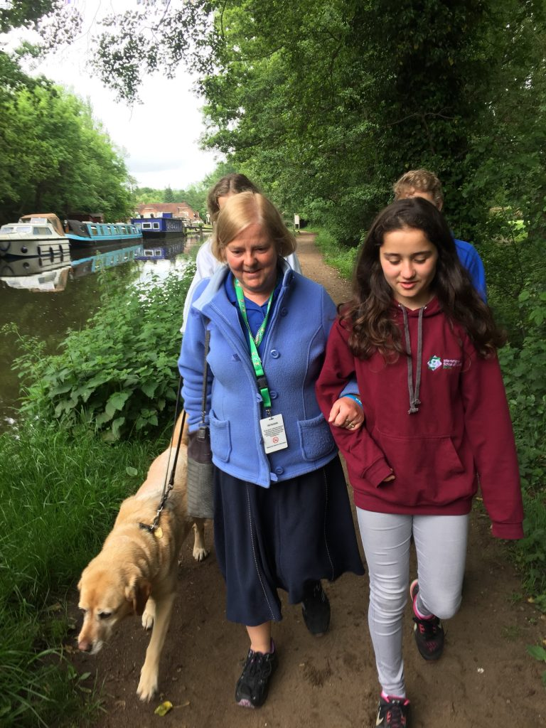 Hilary and her guide dog Yalena walking alongside a canal, being guided by students from the International School of London, Surrey.