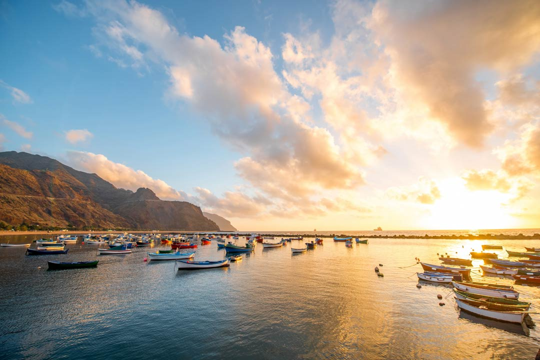 Calm waters filled with traditional fishing boats with a yellow sunset behind it