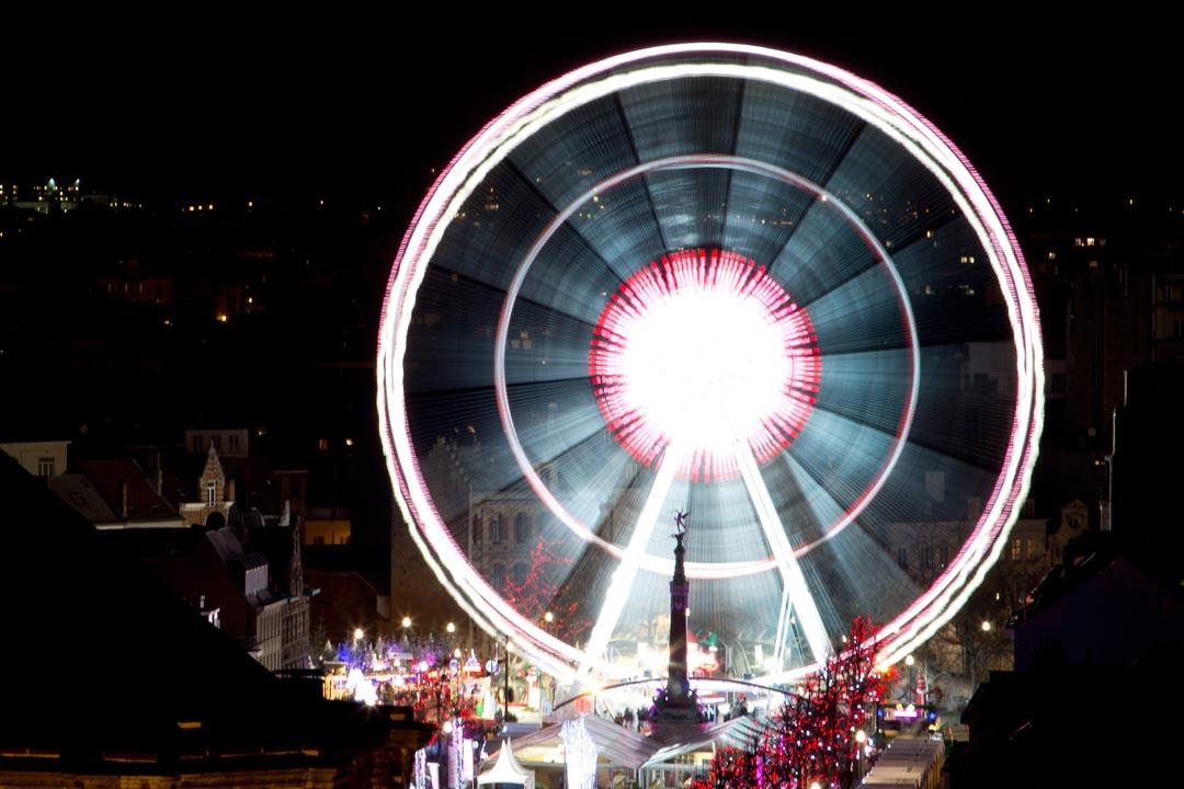 A ferris wheel illuminating a medieval town
