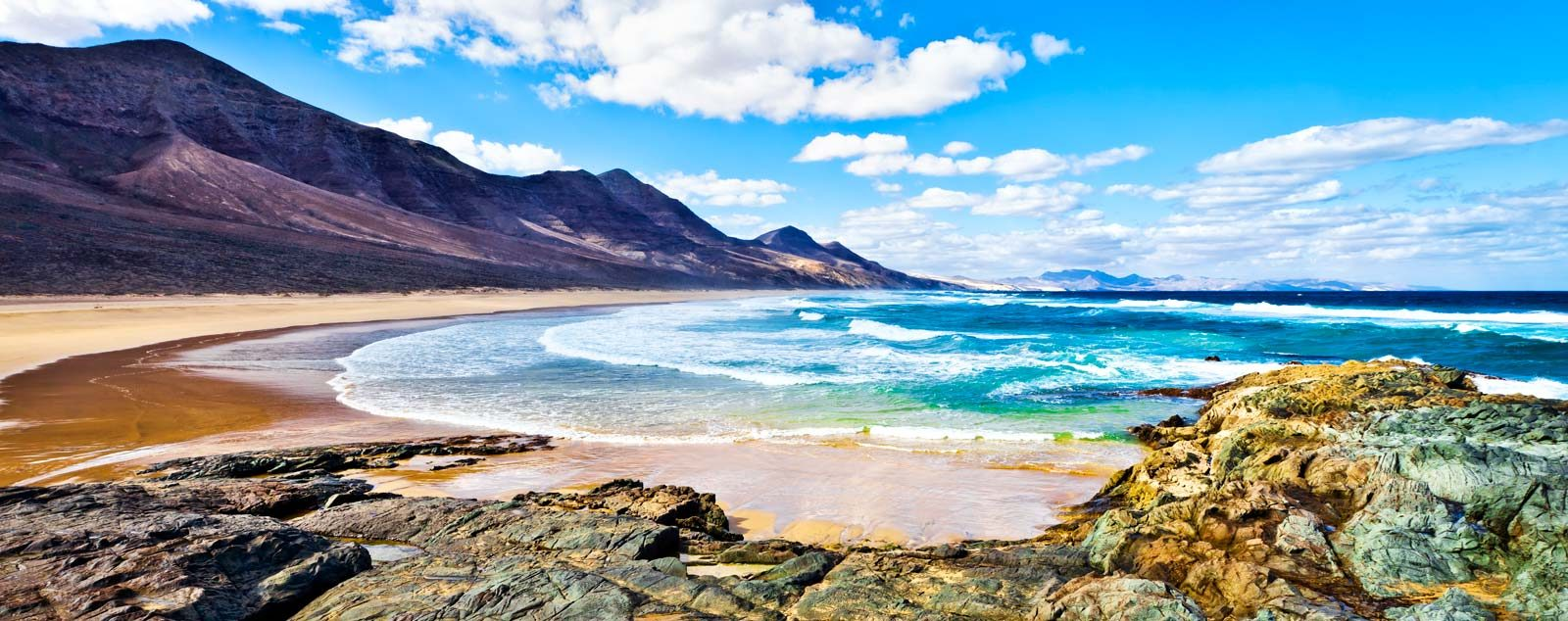 Dark rocky hills lead to pristine yellow sands that are being touched by light blue waves