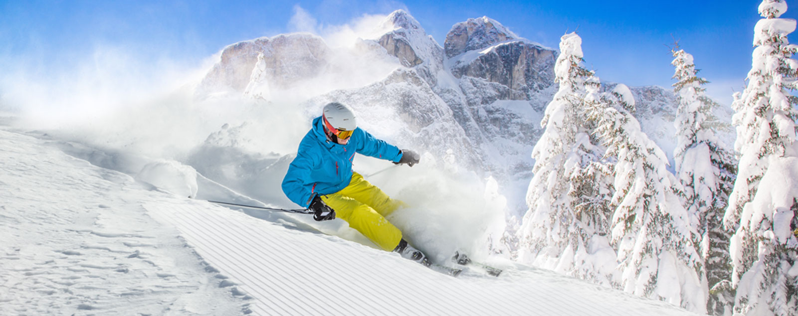 A skier making a parallel turn on a slope next to Alpine trees forms a large cloud of snow in his wake