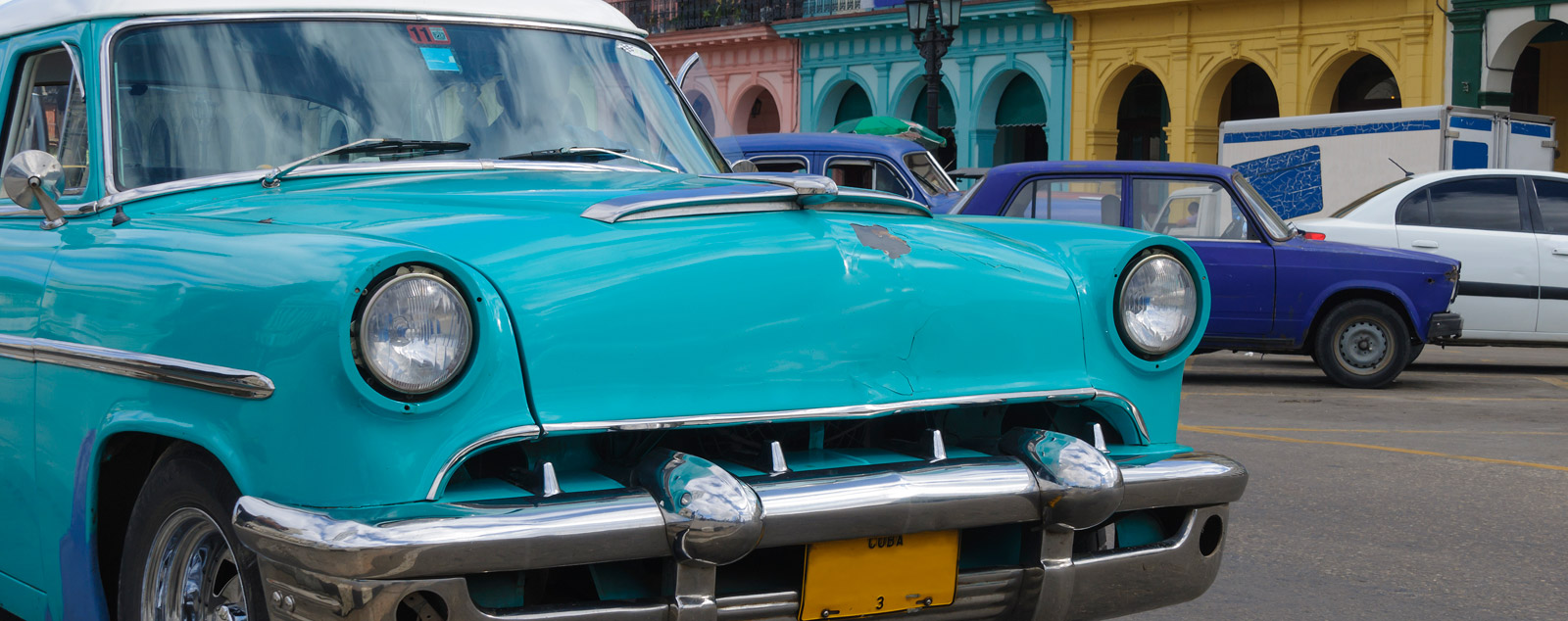 A vintage teal car with circular headlights in the foreground with colourful colourful colonial buildings behind it.