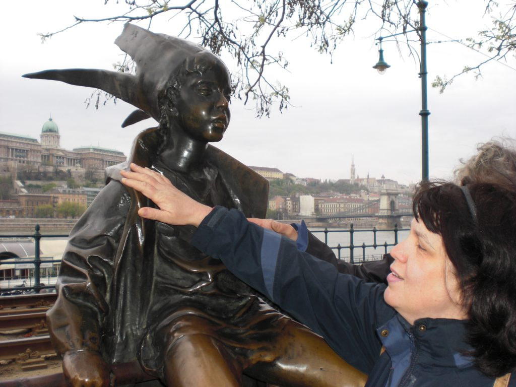 Liz feeling a bronze statue 'The Little Princess statue' in Budapest, Hungary