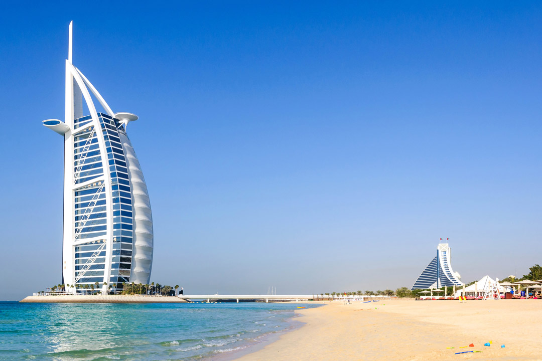 The iconic Burj Al Arab Jumeirah hotel rises out of the Ocean next to a yellow beach