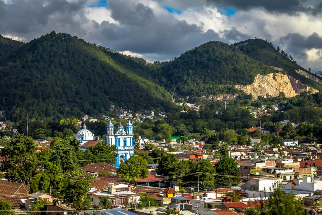 A lush valley filled with red-roofed houses with a white and blue decorated baroque church rising out of the trees