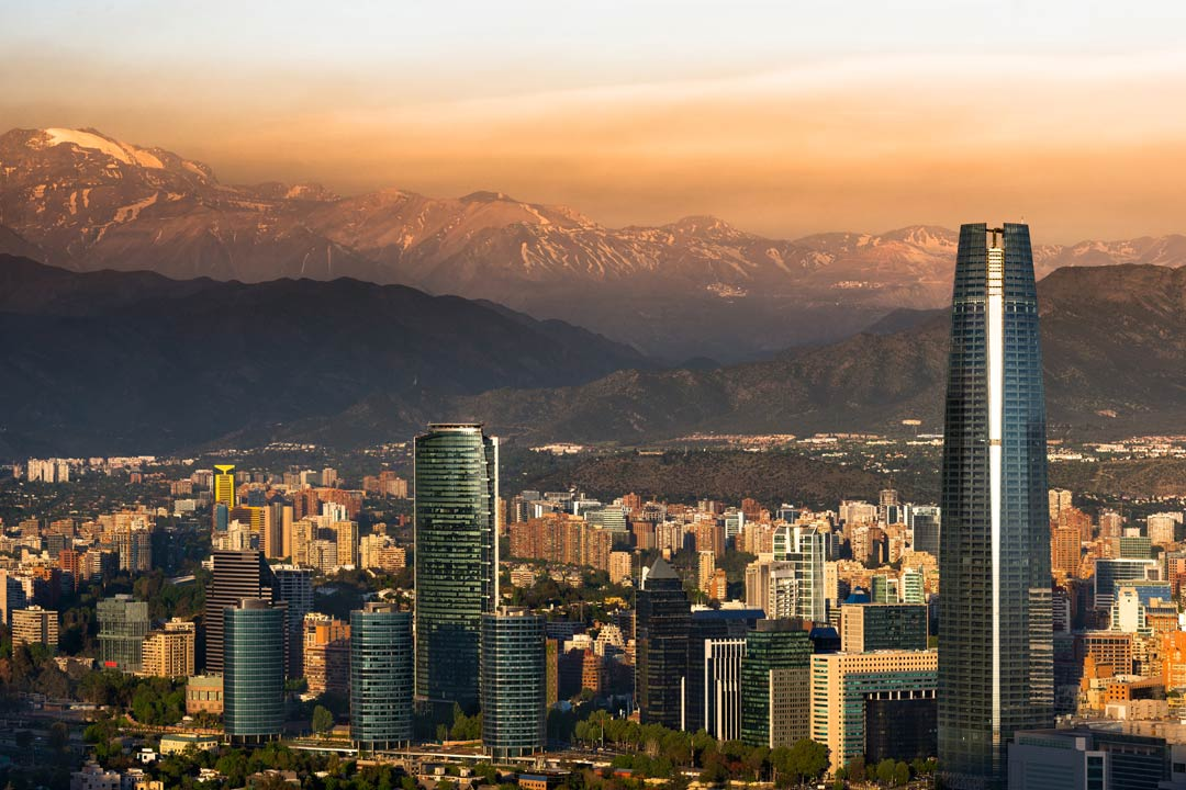 Tall towers line a valley with mountains in the background in Santiago