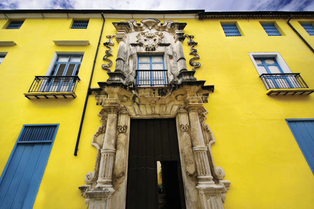 A yellow building with baroque stone detailing around the doors