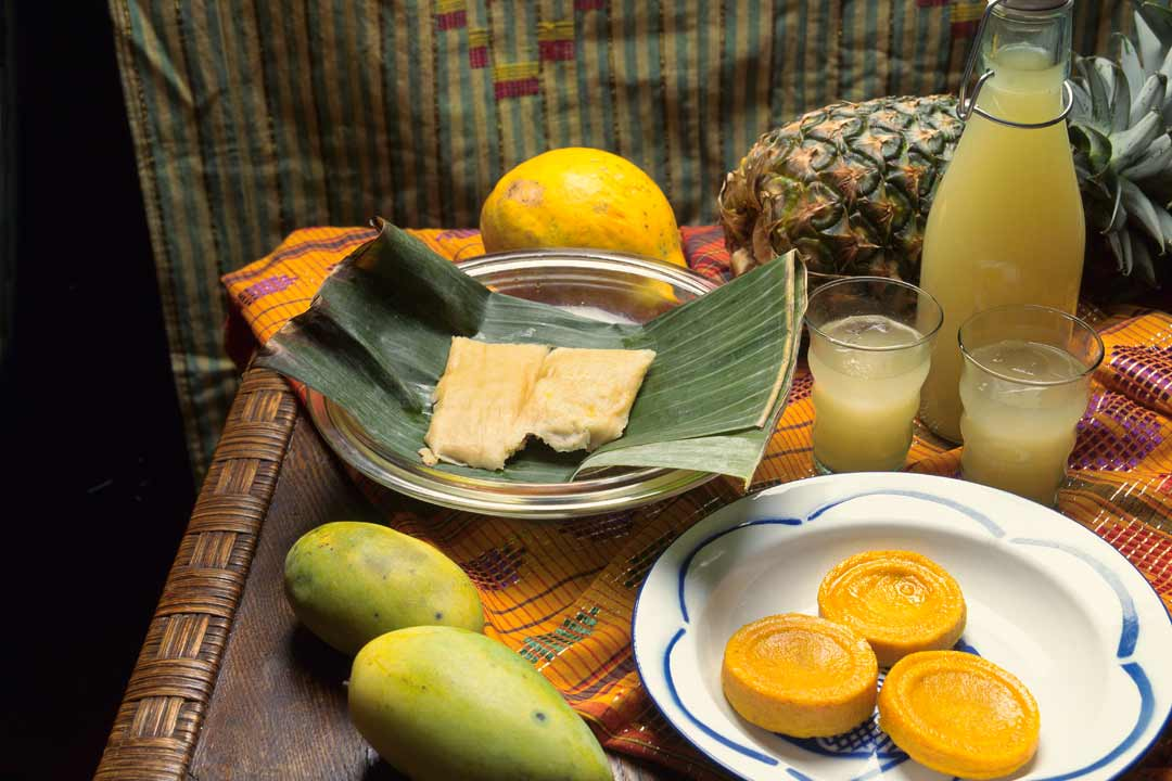 A table laid with traditional refreshments and fruits like mango and juice
