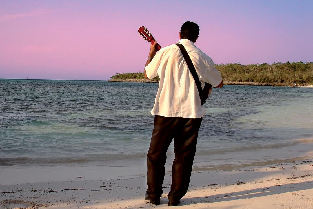 A Cuban man faces the Caribbean whilst playing a guitar