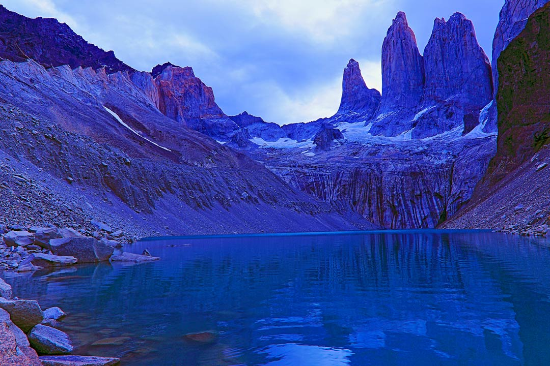 Blue waters of a Chilean fjord leading to unique rock formations in tall peaks