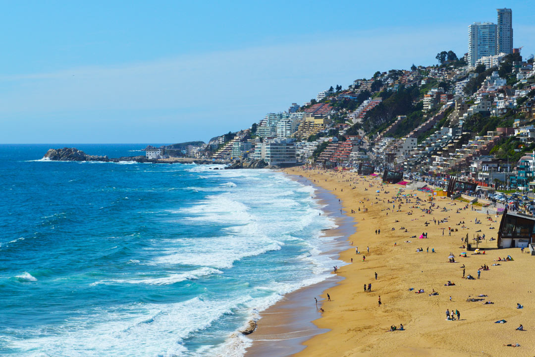 A golden beach next to the blue sea with colourful apartments descending a hill leading to the sands