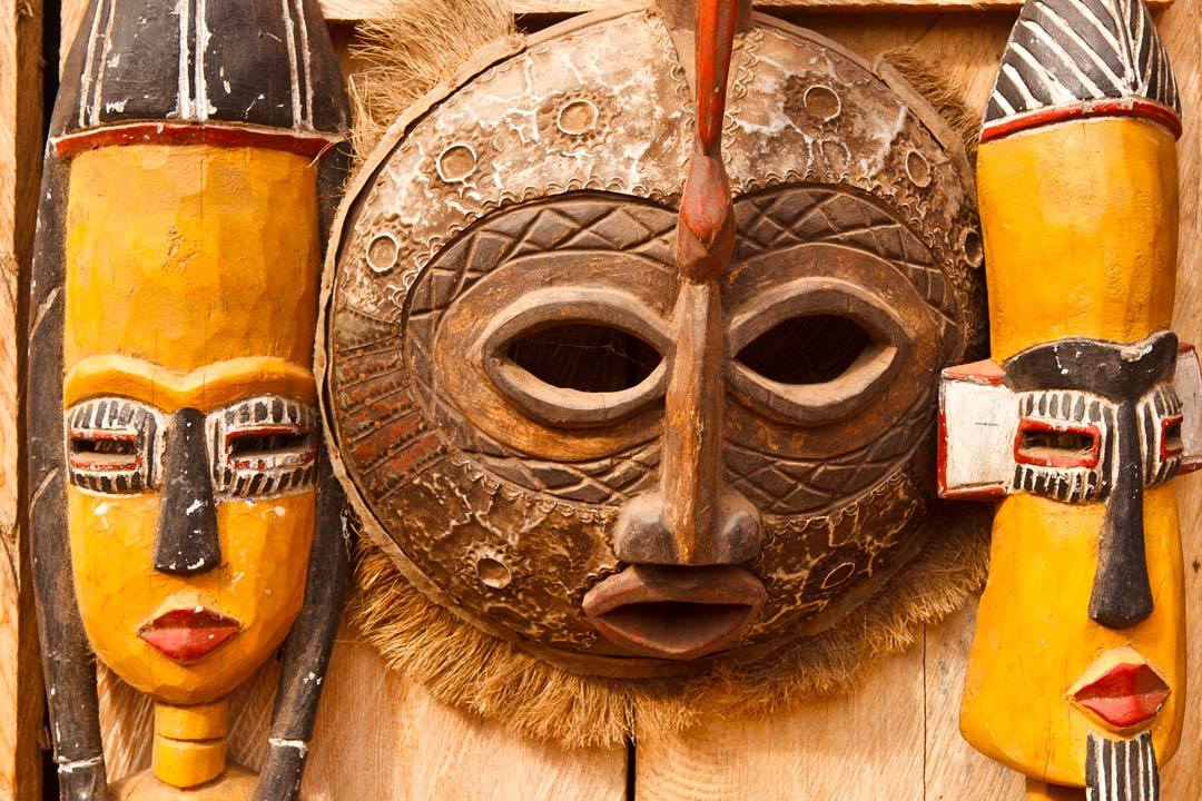 Traditional African face masks carved out of wood and painted yellow