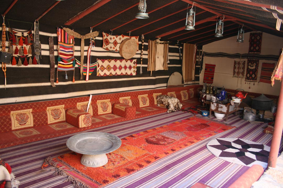 The traditional interior of a Bedouin desert tent filled with carpets, lanterns and tea pots