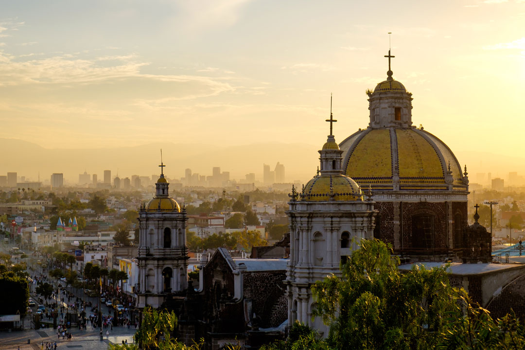 A large baroque cathedral with a golden roof rises out of Mexico City