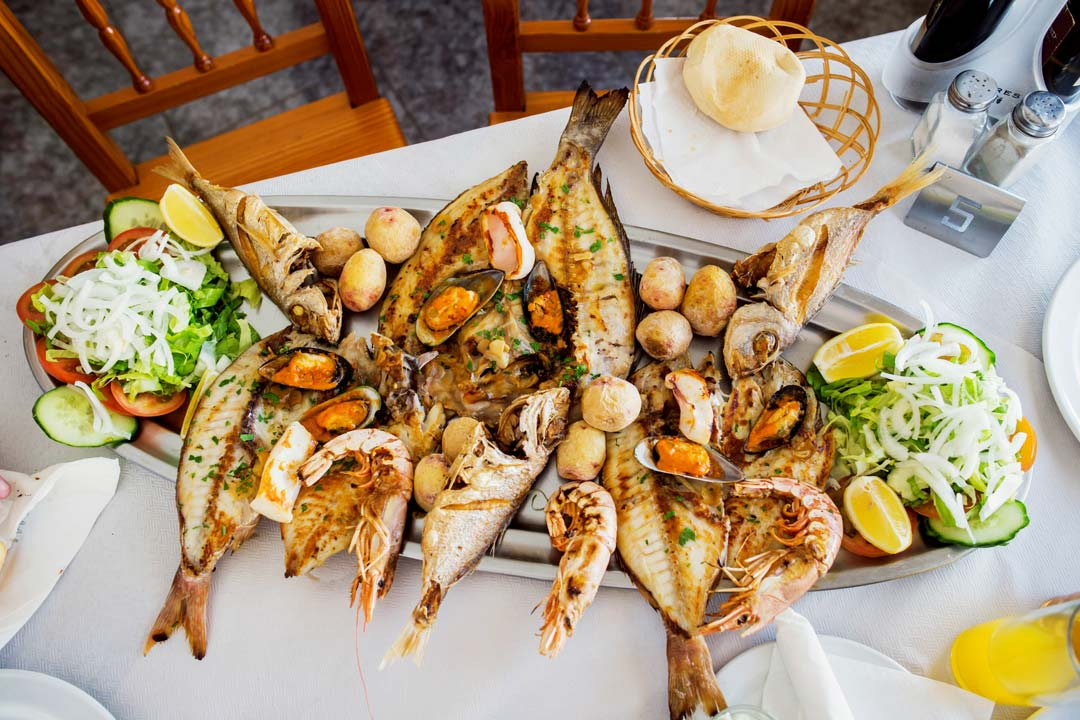 A platter of fish and Canarian potatoes on a silver platter