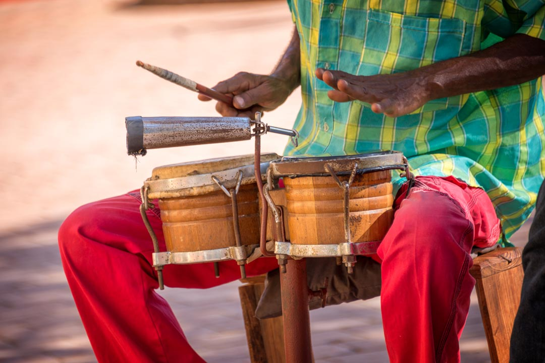 A Cuban man playing the bongo drums with his hand and a drum stick