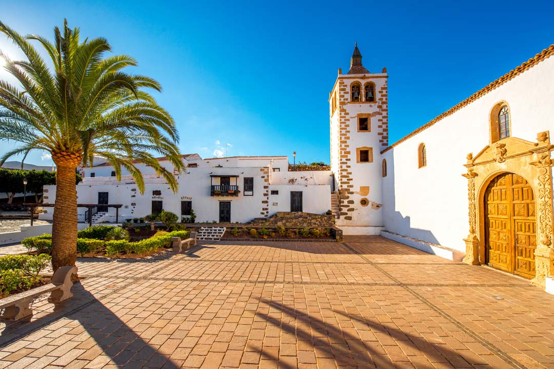 A traditional Canarian church building painted white with a bell tower and ornate door
