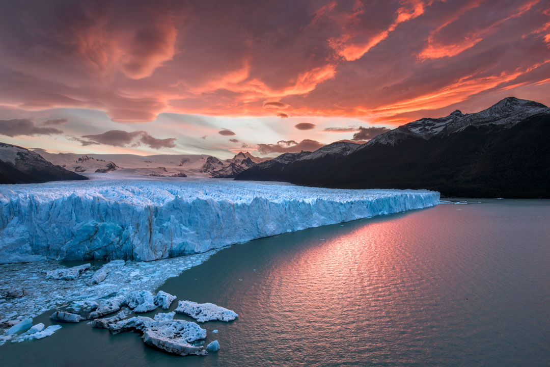 A white glacier with tones of blue rises high out of a body of water