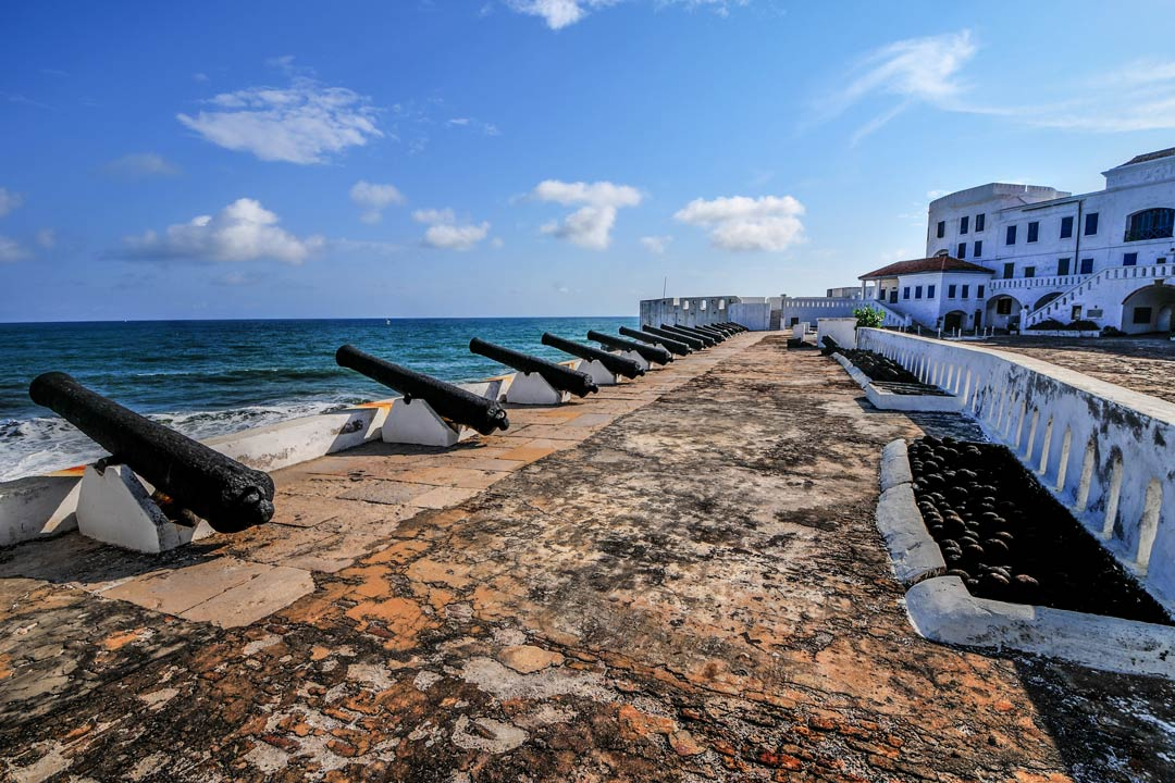 A row of cannons face out to the sea in an old white colonial fort