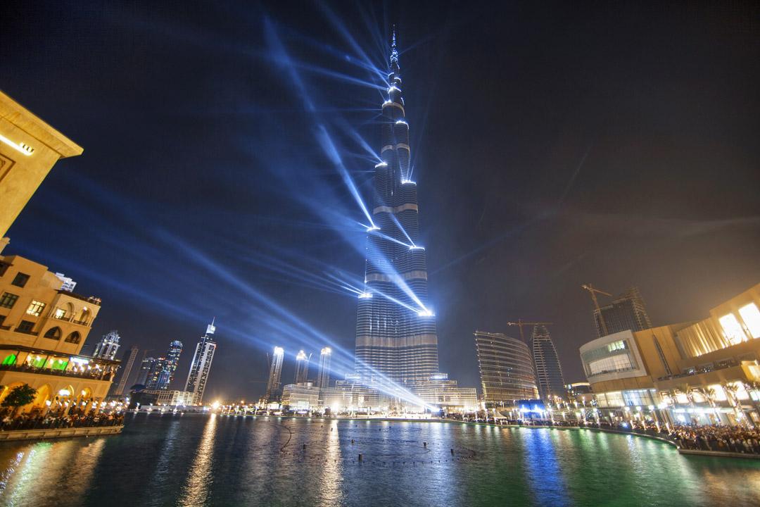 The Burj Khalifa rises into the night sky illuminated by many lights