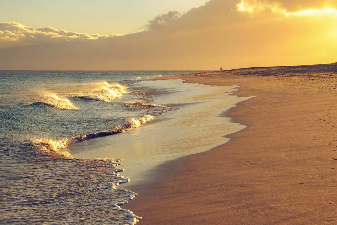 A yellow sun setting on blue waves lapping against a yellow beach