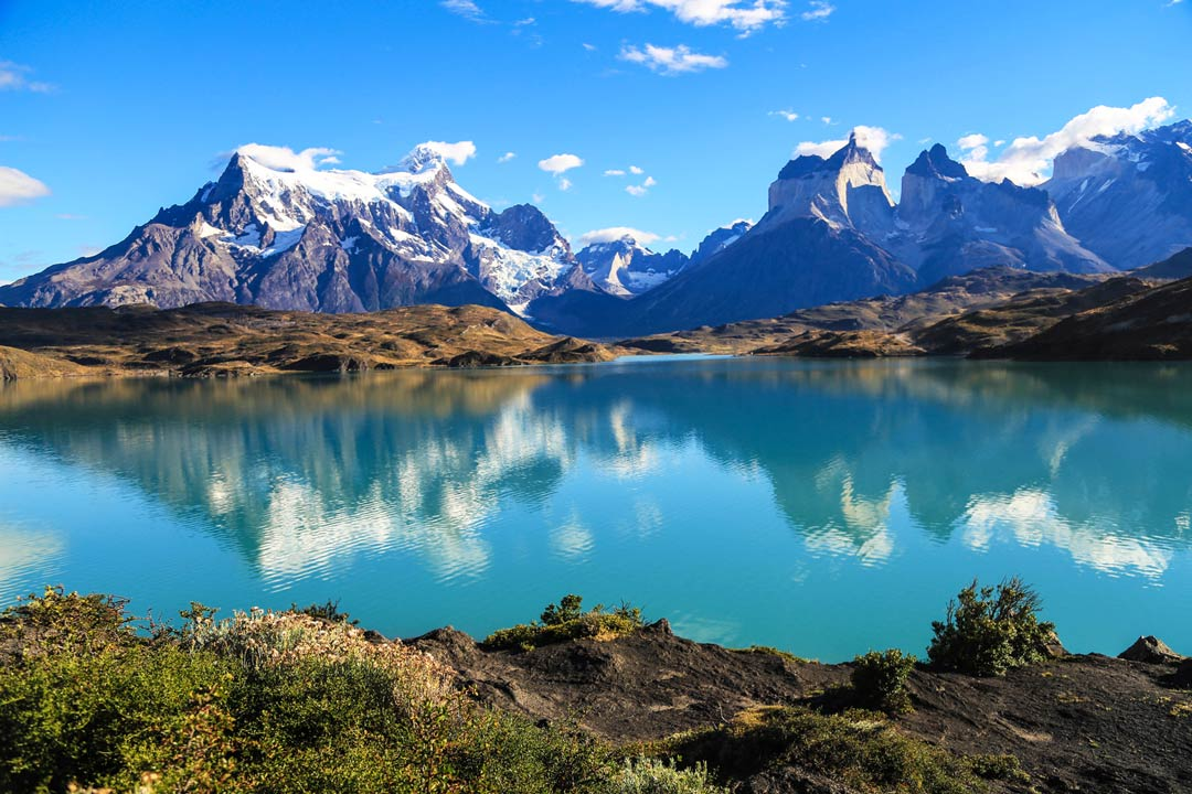Turquoise waters reflect snow-capped peaks in the background