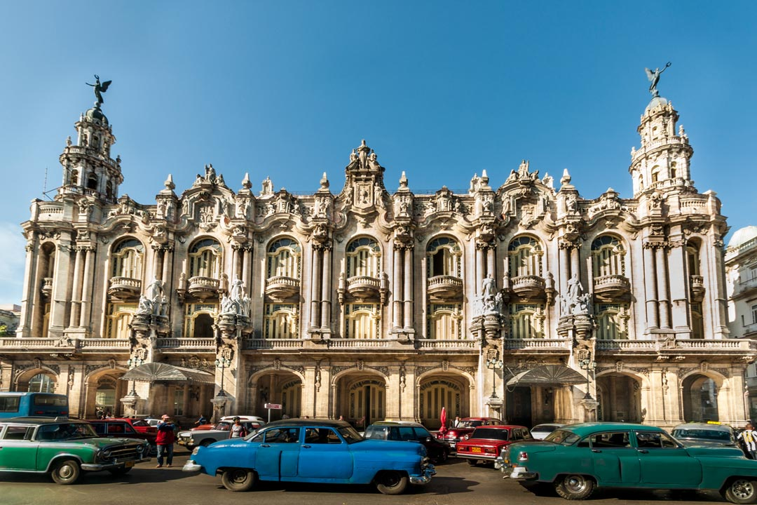 The ornate facade of the Gran Teatro de la Habana drenched in sunlight with Cuban cars driving past.