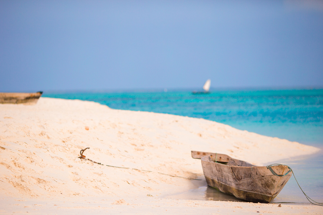 A wooden canoe boat anchored on white sandy shores next to the blue ocean