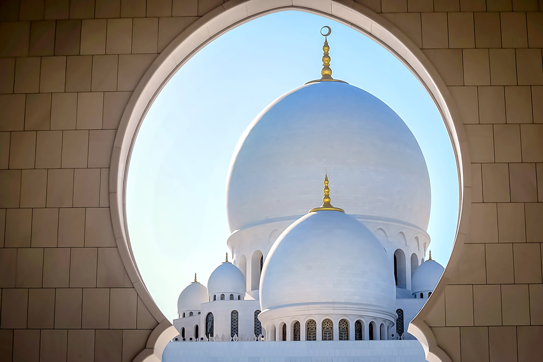 Two large white domes topped by golden crescent moons seen through a Moorish arch