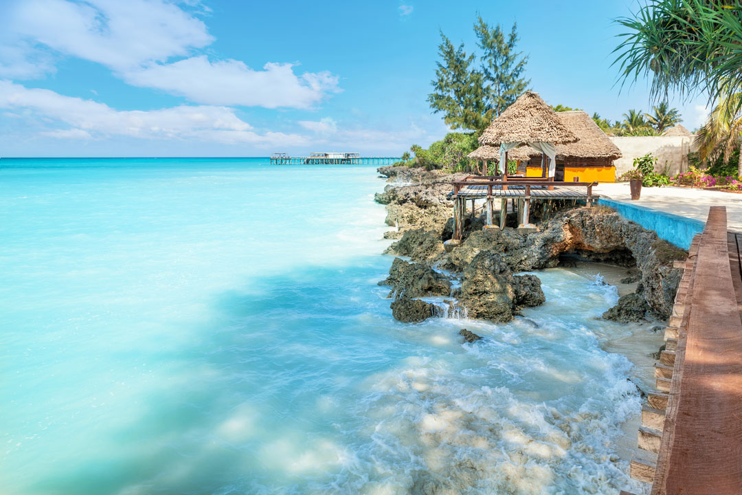 A thatched beach hut sits next to clear azure waters