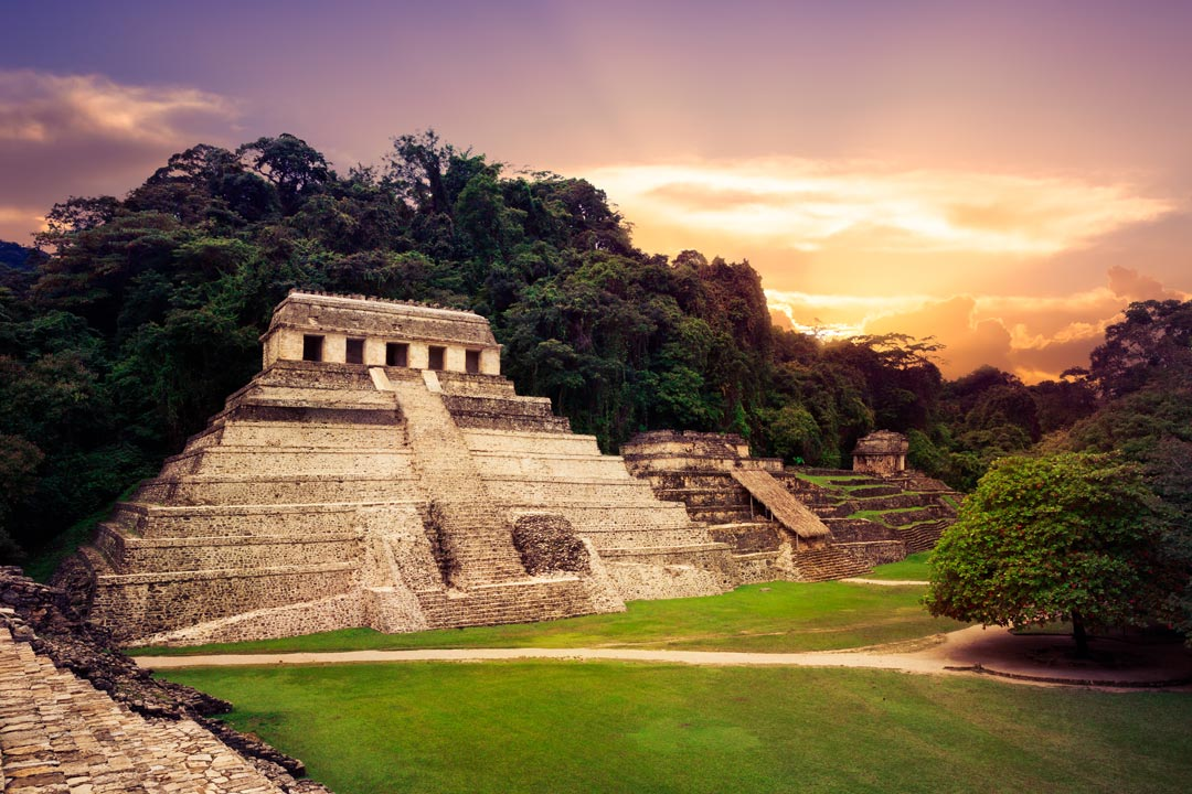 A row of stepped temples in pristine condition surrounded by lush rainforest