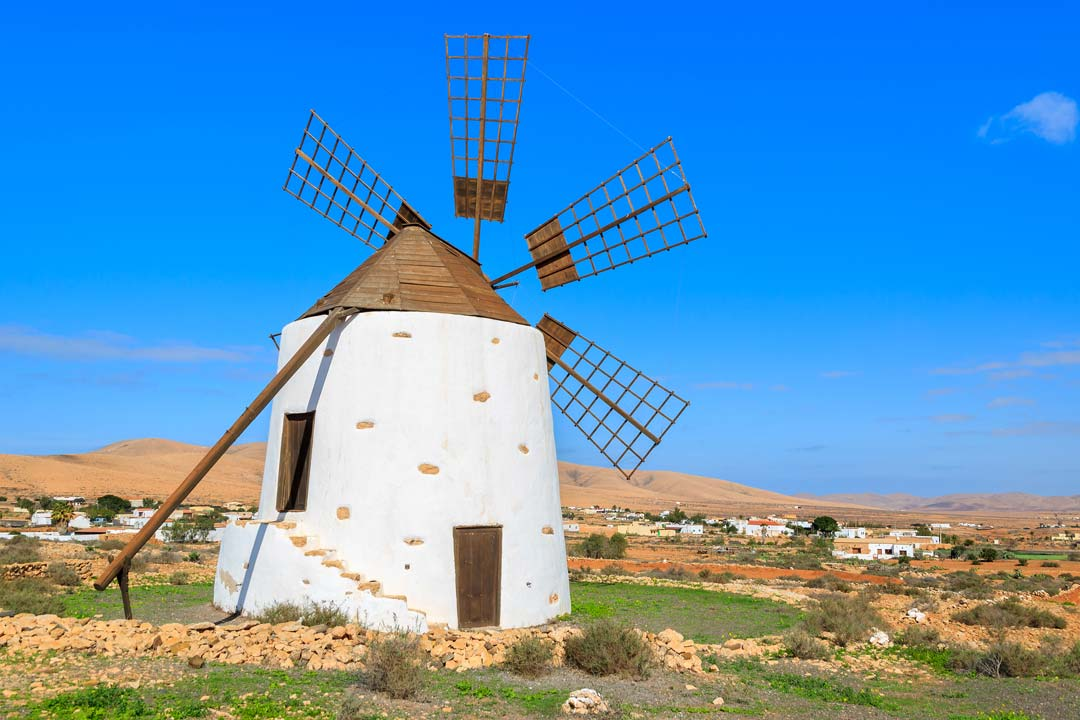 A traditional white windmill stands under a clear blue sky