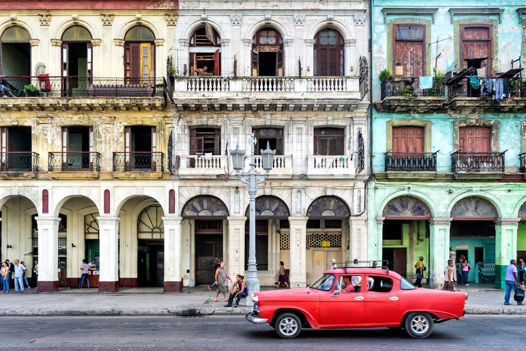 A red vintage car being driven past colonial coloured buildings