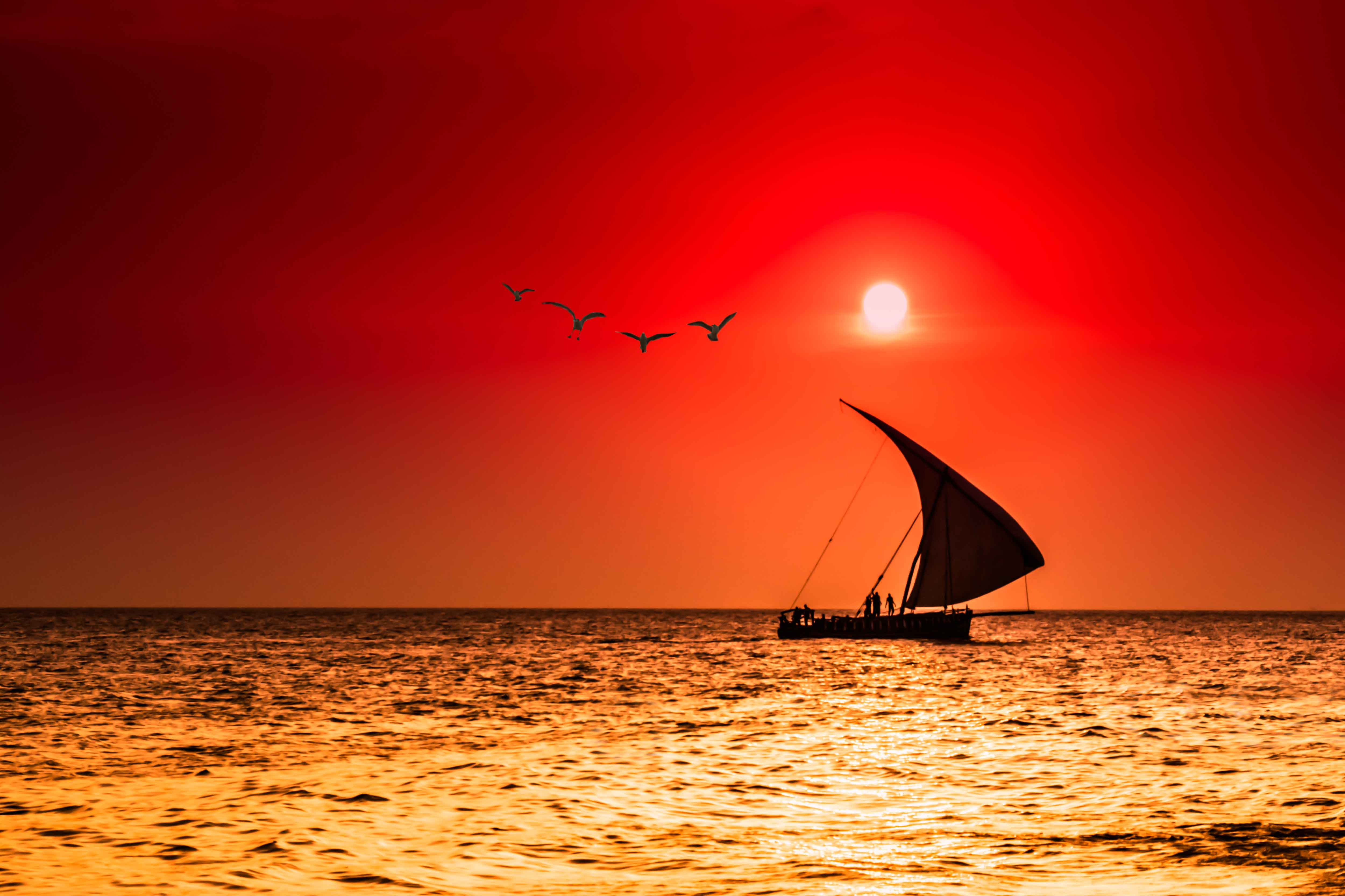 A traditional dhow sailing through calm waters underneath a red sunset