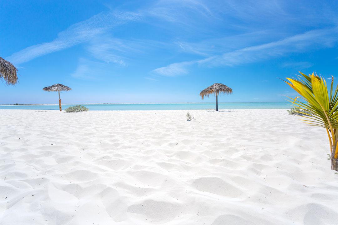Softa white sand under a clear blue sky