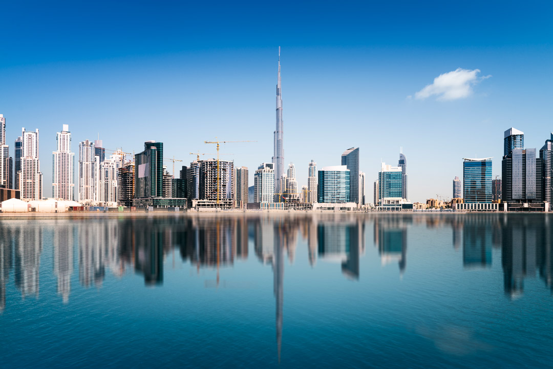 The futuristic cityscape of Dubai with huge skyscrapers next to calm blue waters
