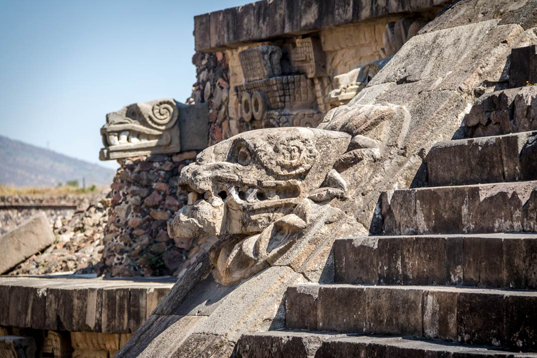 A carved relief of a demon on the side of a stepped temple