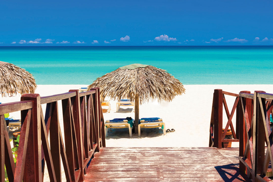 A wooden walkway leads to pristine white sand and turquoise waters