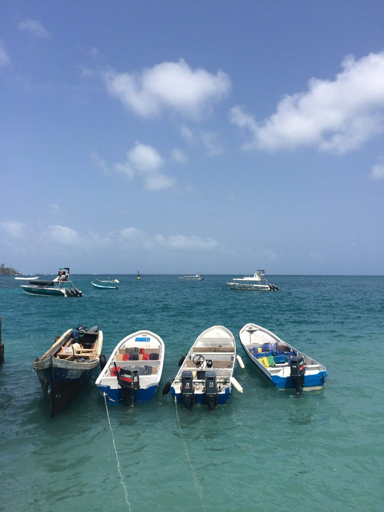 Image of four boats tied up at the shore. Clear blue waters and only two small clouds in the sky