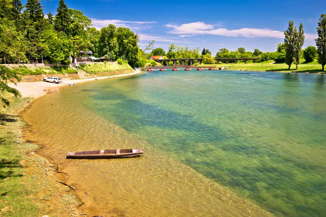 A wooden boat is moored on a clear river's bank. The water is tranquil and there are sand beaches and green trees lining the bank