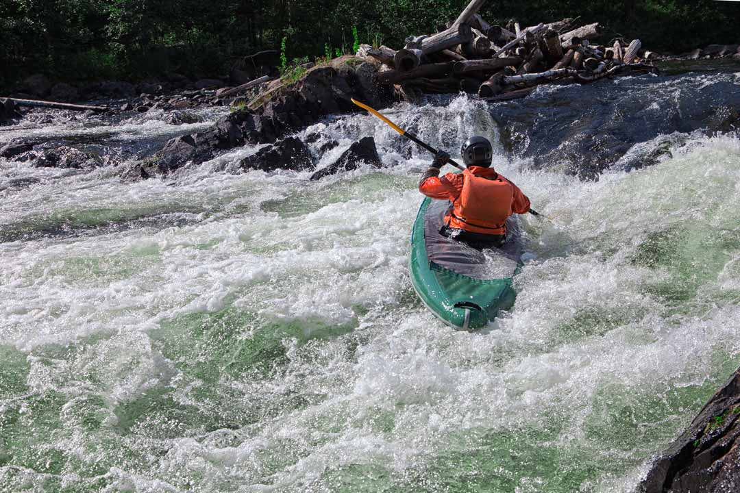 A canoeist is journeying down the river with white water rapids on either side