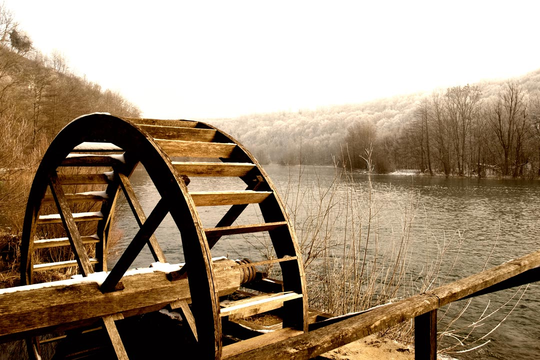 An old wooden mill sits on the rivers bank. Dense forest lines the banks of the wide and calm river
