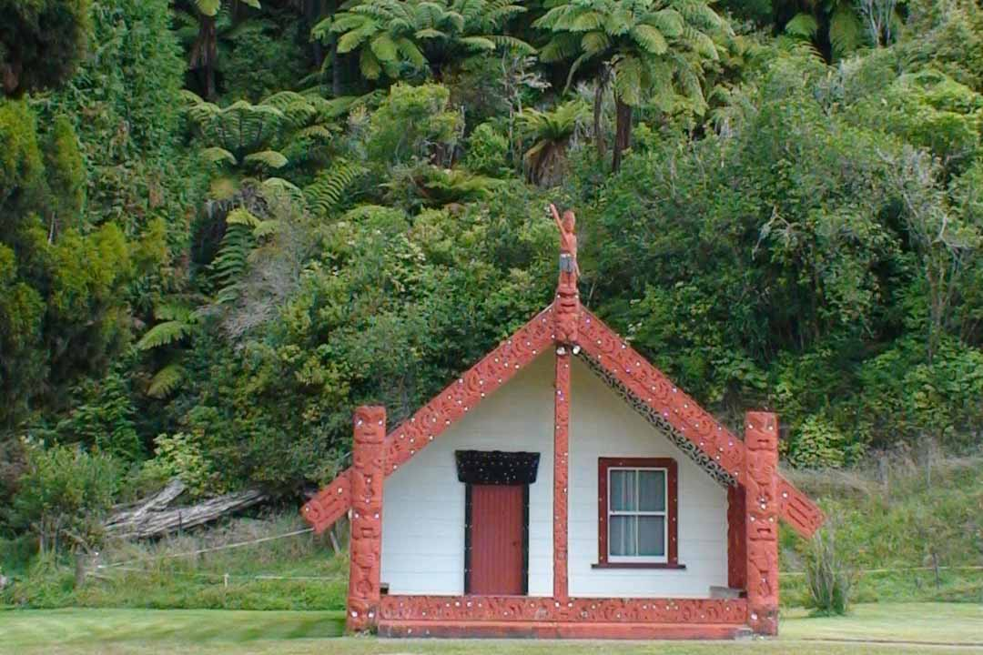 A traditional Maori home with carvings attached, green forest in the background
