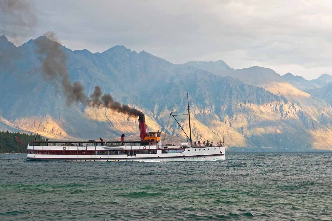 A traditional steamer chugs across a lake, with steep rocky cliffs in the background