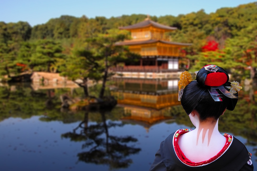 A Geisha with her hair done up and white make-up on her back stares across a lake towards a temple