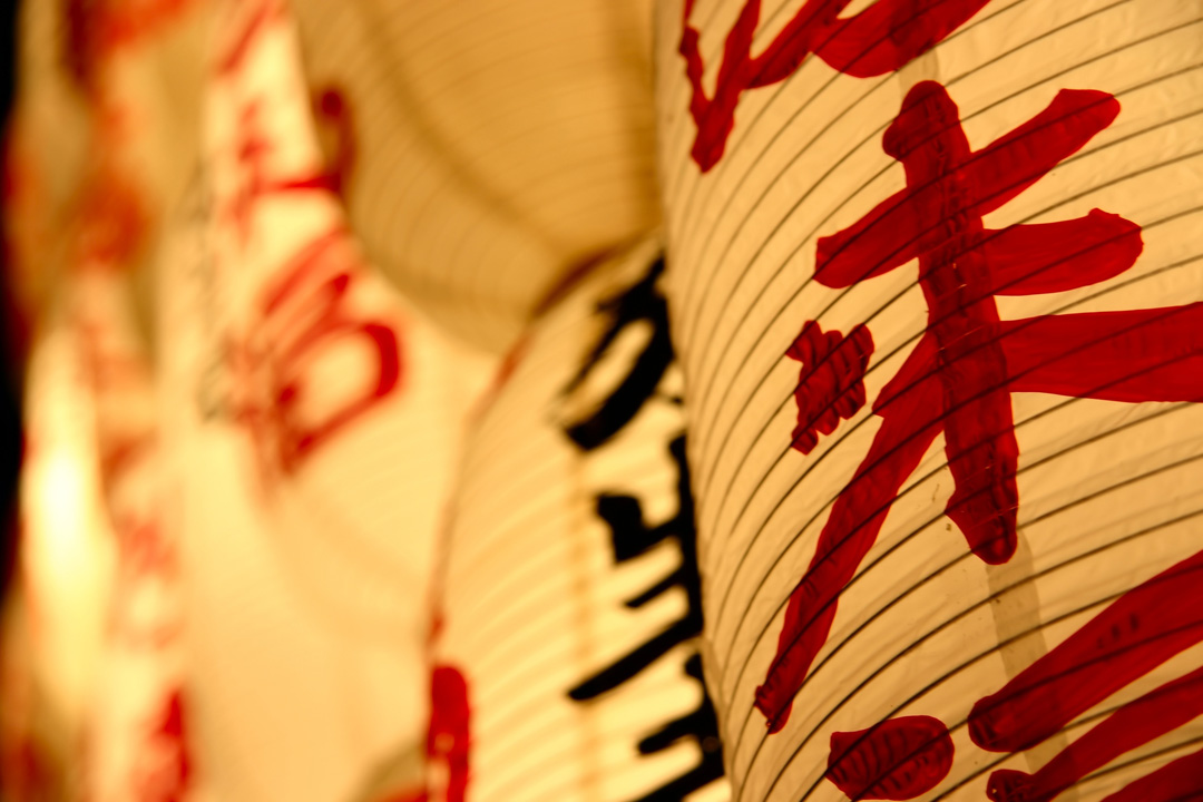 Thine paper lanterns with Japanese writing on them in red paint