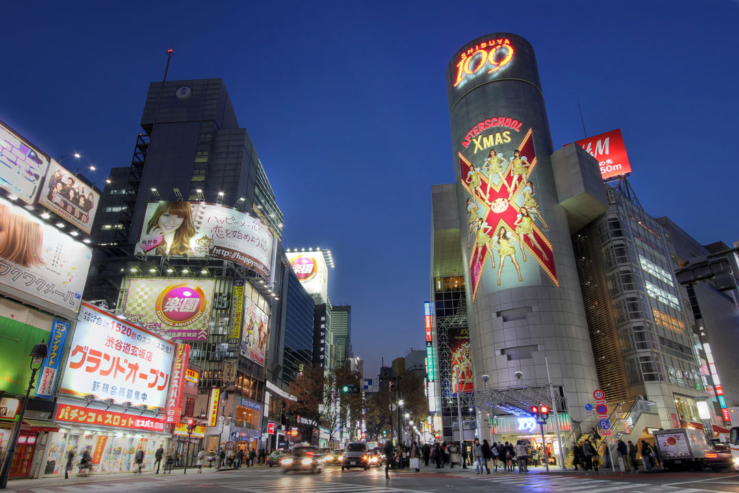 A busy urban scene in Tokyo with bright lights and advertisements.