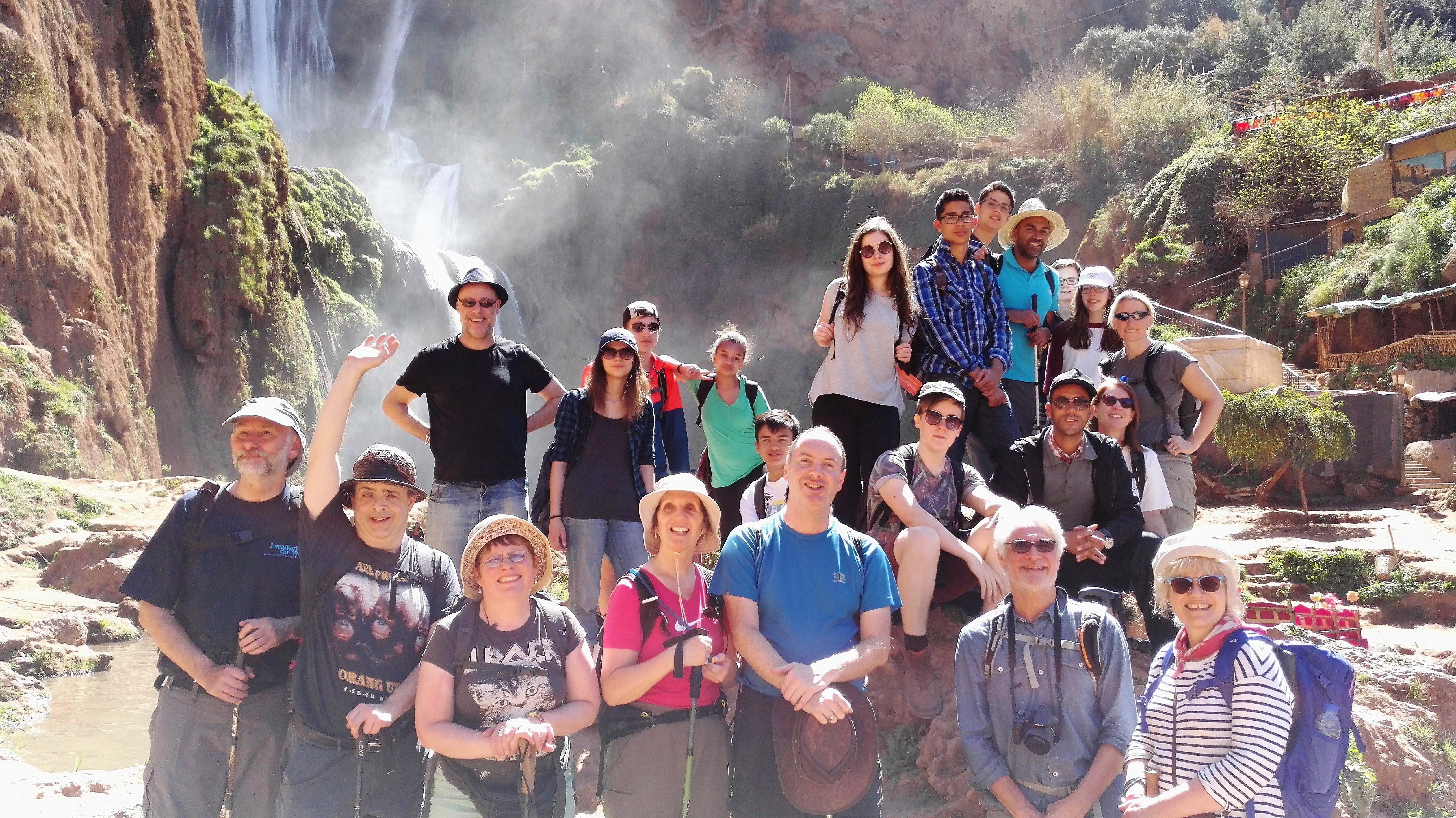 Image of international school students with visually impaired travellers in front of a waterfall.