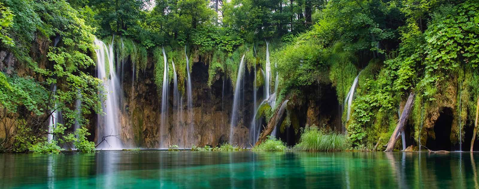 Waterfalls cascade down through greenery and into a still pool